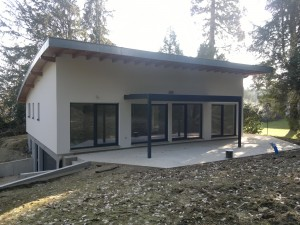 Maison en ossature bois avec toiture cintrée et terrasse. Vue arrière.