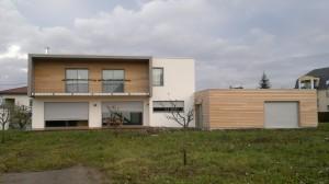 Maison à ossature bois avec toit plat. Garage à toit plat avec bardage. Vue arrière.