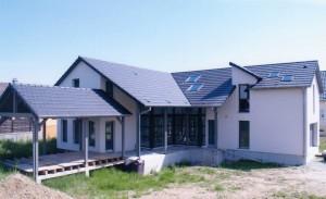 Maison en ossature bois avec grande baie vitrée et terrasse en bois.
