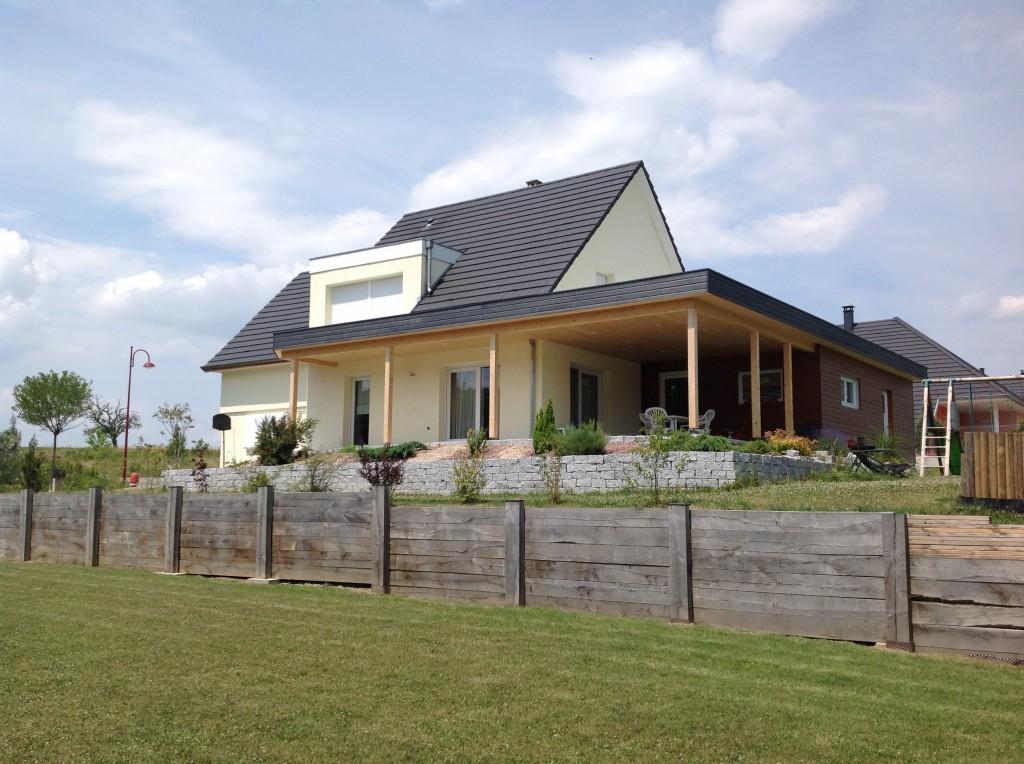 Extension d'une maison avec terrasse couverte en bois et garage en bois